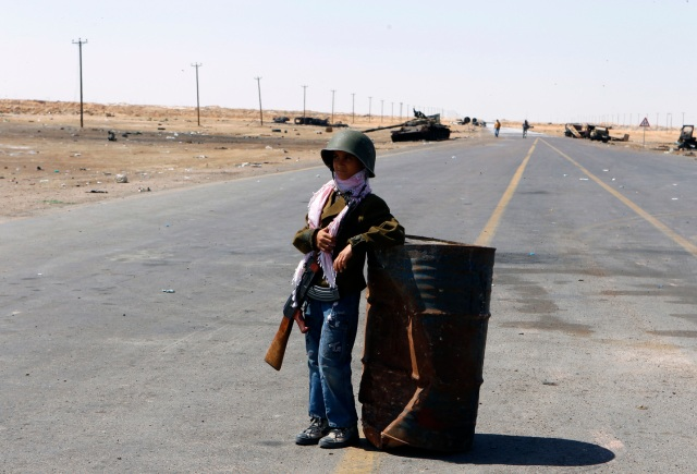 Mohamed, 10, stands guard at the frontline along the western entrance of Ajdabiyah